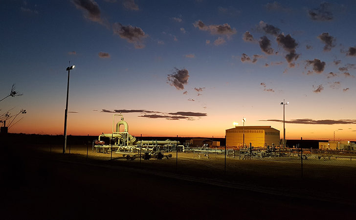 An orange glow on the horizon fills the morning sky behind Beharra Springs Gas Plant