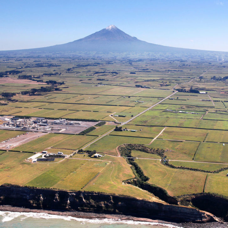Image of coast line, green fields, Kupe Basin Gas Plant and the snow-capped peek of Mount Taranaki rising high on the horizon