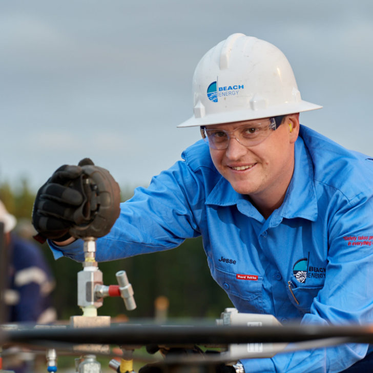 Beach Energy staff member wearing a hard hat and gloves while checking pressure gauge at a gas plant