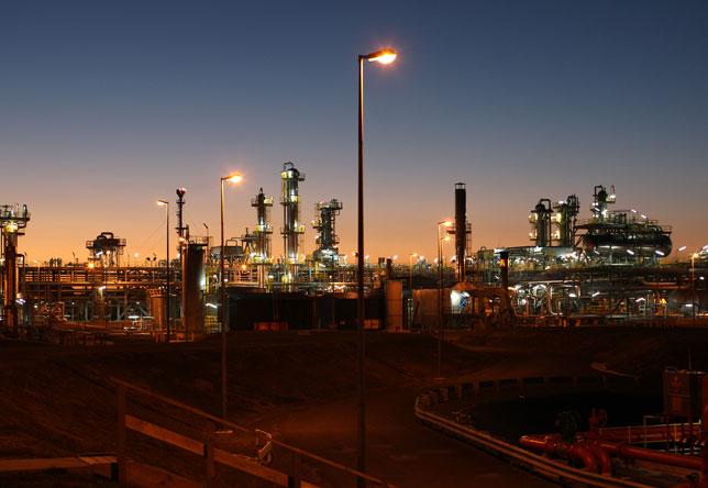 Bright lights shine from Kupe Gas Plant, New Zealand, with soft blue orange hues of the sunrise filling the sky