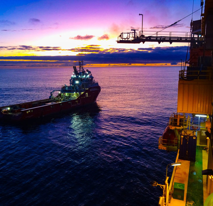 Pink and purple hues wash over the Yolla Gas Platform and cargo ship on sunrise