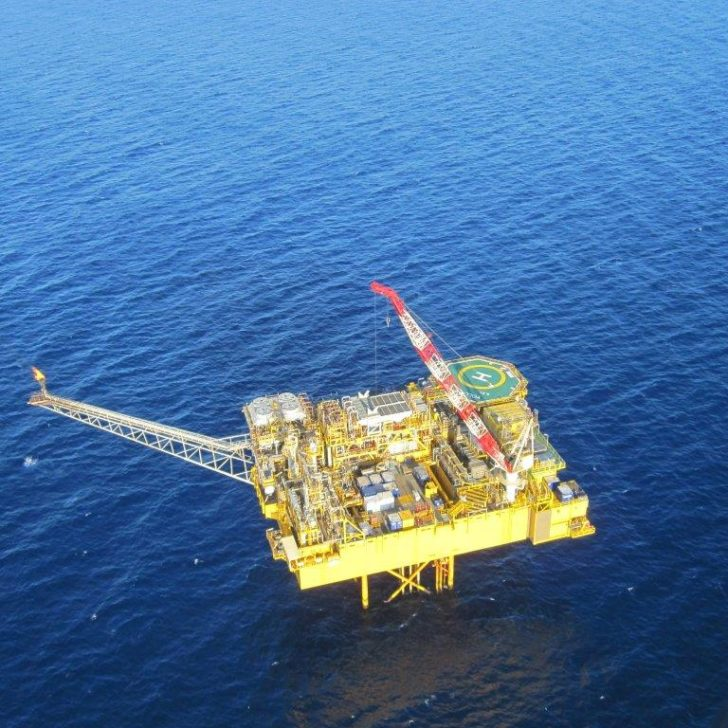 Image of the bright yellow Yolla Offshore platform sitting alone and surrounded by a vast blue ocean